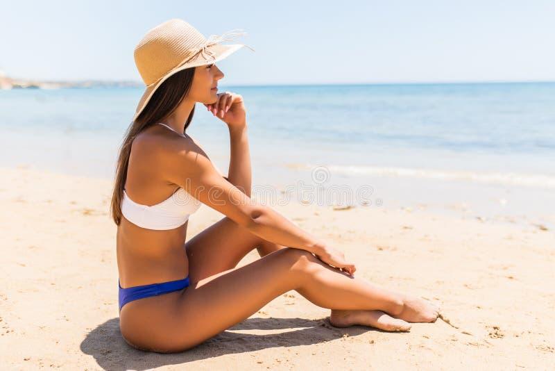 Junge lateinische Frau im Strohhut, der auf tropischem Strand liegt stockbilder