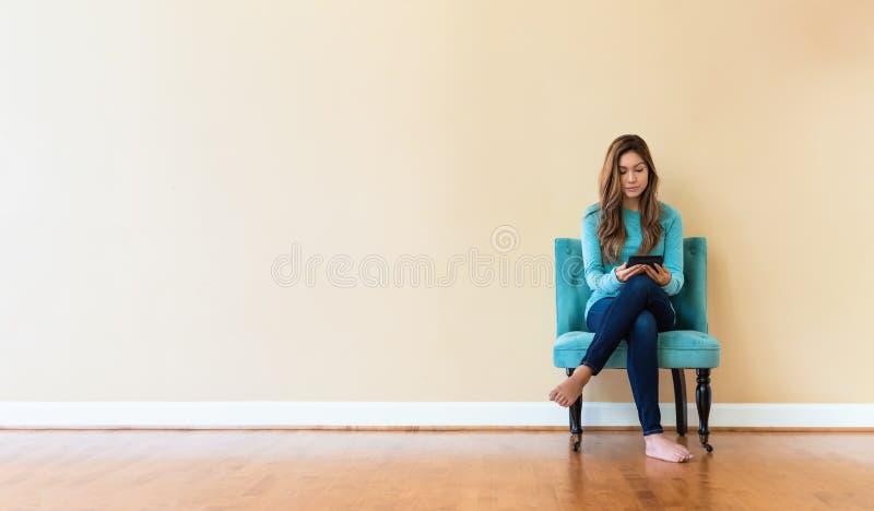 Junge Latina-Frau mit einem Elesergerät stockfoto