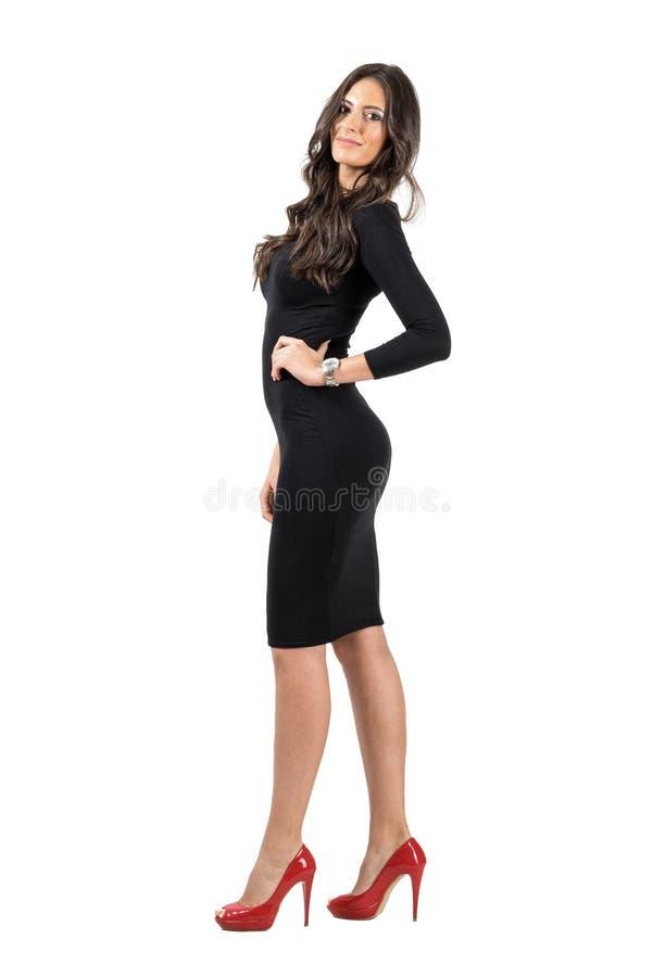 Junge LatinoGeschäftsfrau im kurzen schwarzen Kleid, das an der Kamera aufwirft stockbild