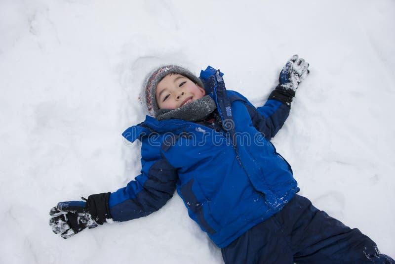 Junge legt im Schnee nieder. lizenzfreie stockbilder