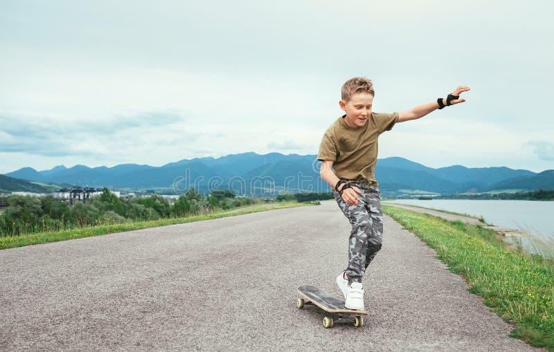 Junge lernen, auf Skateboard eiszulaufen stockbild