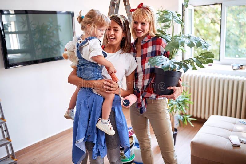 Junge lesbische Paare, die in neues Haus mit einem Kleinkindmädchen sich bewegen lizenzfreies stockbild