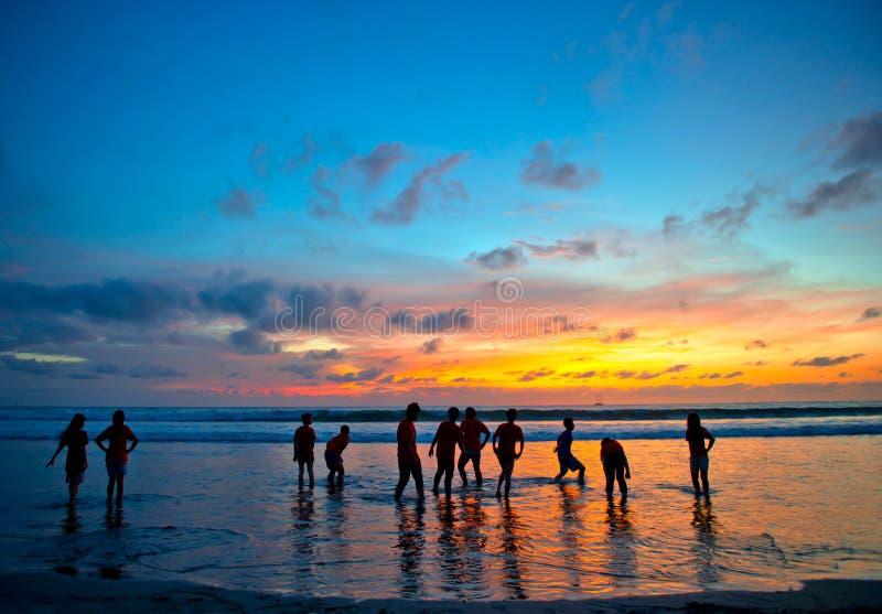 Junge Leute bei Sonnenuntergang setzen in Kuta, Bali auf den Strand stockbild