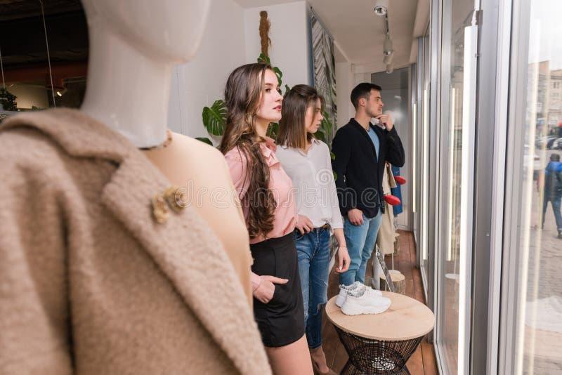 Junge Leute bleiben nahe Mannequin am Schaufenster stockfotografie