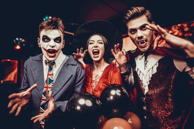 Junge Leute in den Kostümen Halloween feiernd lizenzfreies stockfoto