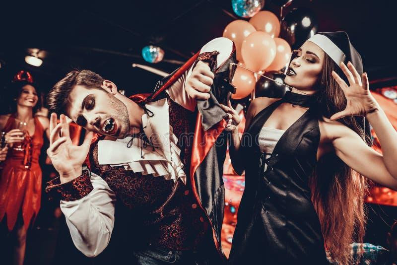 Junge Leute in den Kostümen Halloween feiernd stockfoto