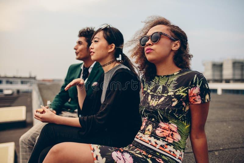 Junge Leute, die auf Dachspitze sitzen lizenzfreies stockbild