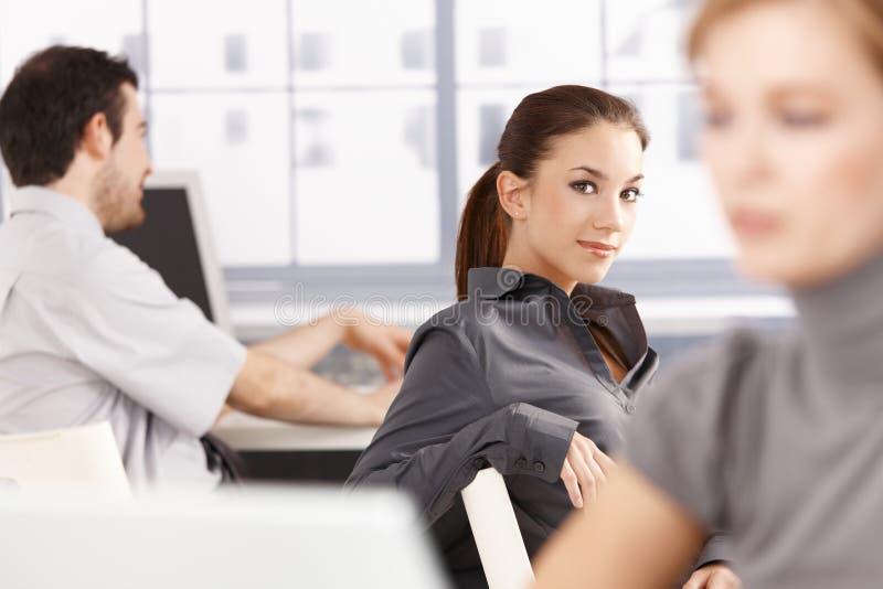Junge Leute, die beim Bürolächeln arbeiten stockbilder