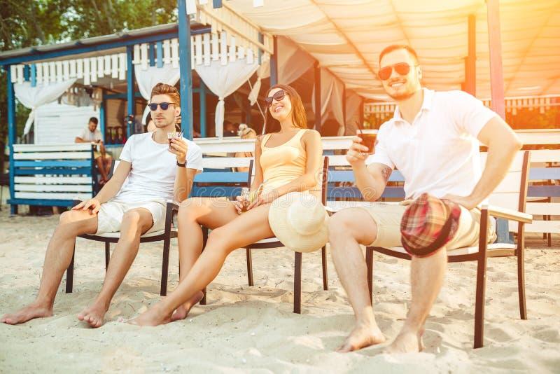 Junge Leute, die das ein Sonnenbad nehmende Trinken der Sommerferien an der Strandbar genießen lizenzfreie stockbilder