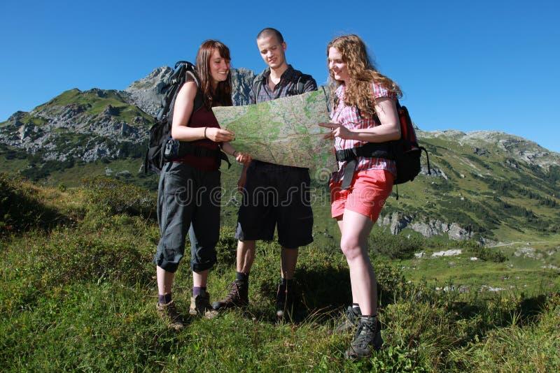 Junge Leute, die in den Bergen wandern lizenzfreie stockbilder