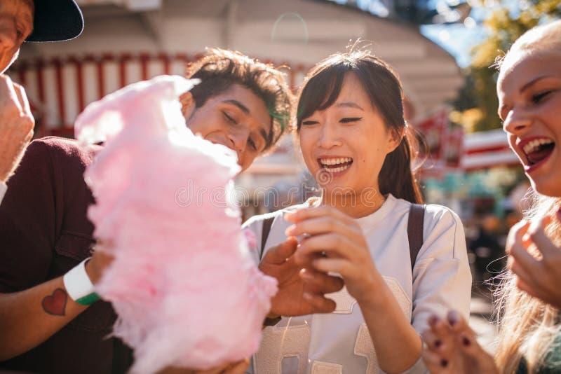 Junge Leute, die draußen Zuckerwatte teilen stockfotografie