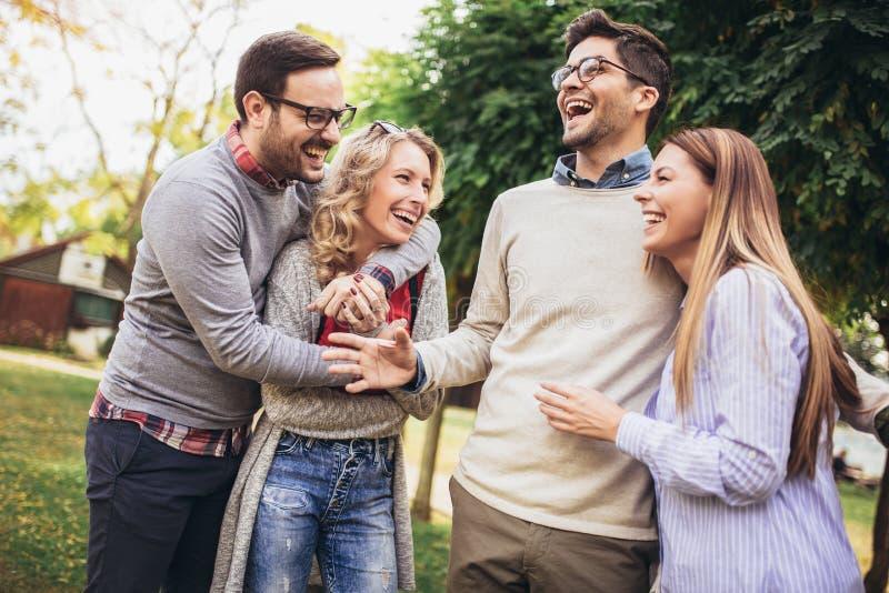 Junge Leute, die durch Park gehen Freunde, die den Spa? im Freien haben lizenzfreie stockfotos