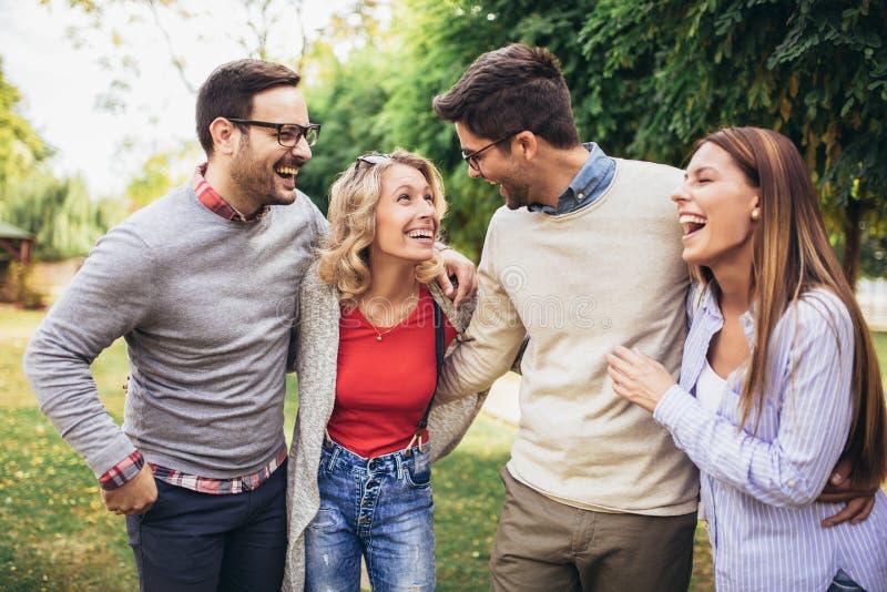 Junge Leute, die durch Park gehen Freunde, die den Spa? im Freien haben lizenzfreies stockfoto