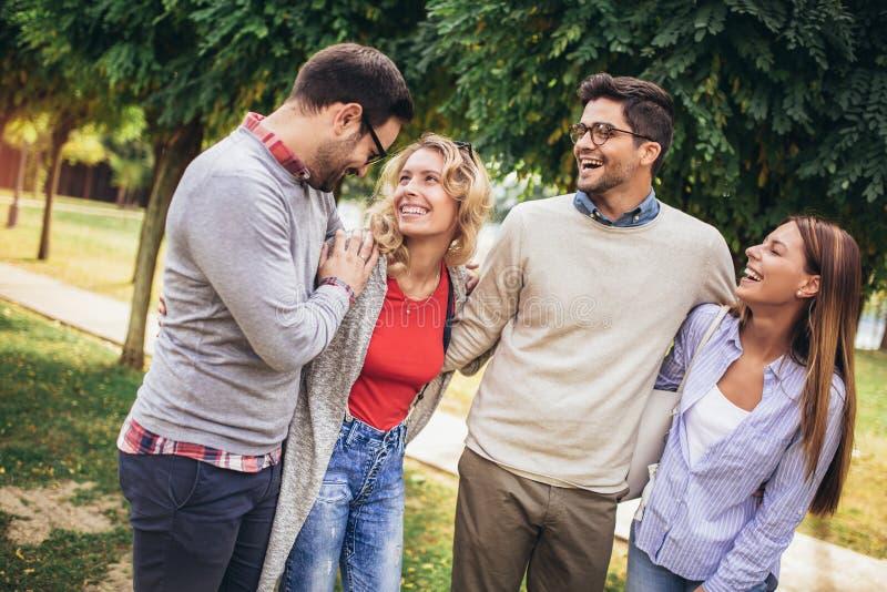 Junge Leute, die durch Park gehen Freunde, die den Spa? im Freien haben stockbilder
