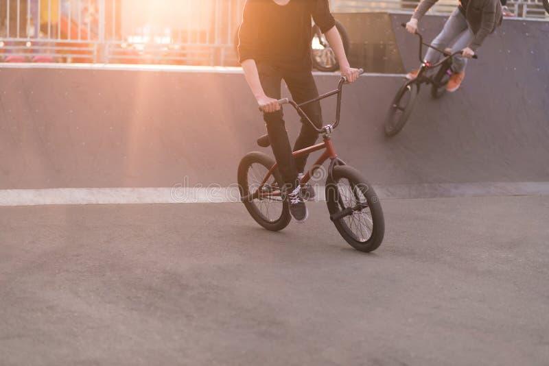 Junge Leute, die ein Bmx-Fahrrad in einem Rochenpark im Hintergrund des Sonnenuntergangs reiten BMX-Konzept Bmx-Fahrrad-Training stockfotos