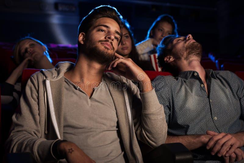 Junge Leute, die einen langweiligen Film am Kino aufpassen lizenzfreie stockfotos