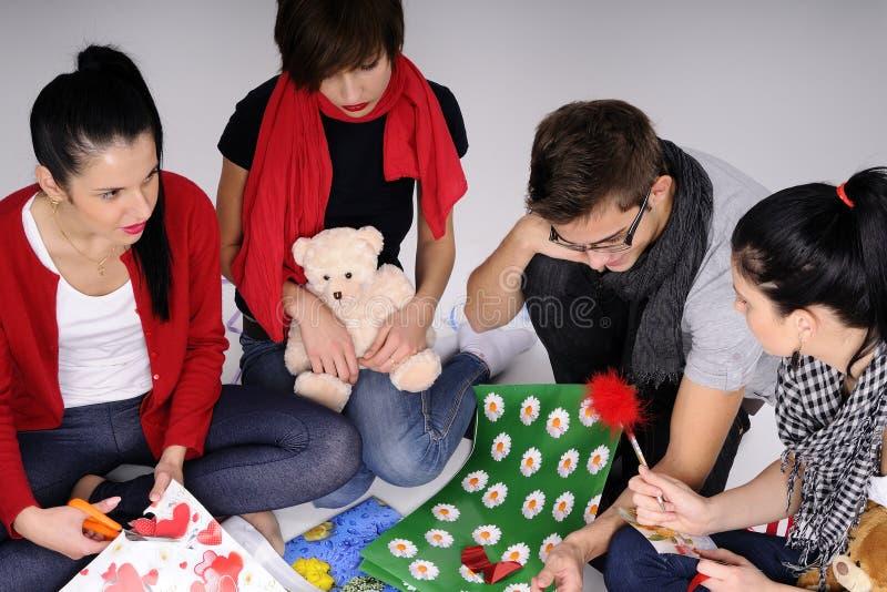 Junge Leute, die Geschenke herstellen lizenzfreies stockbild