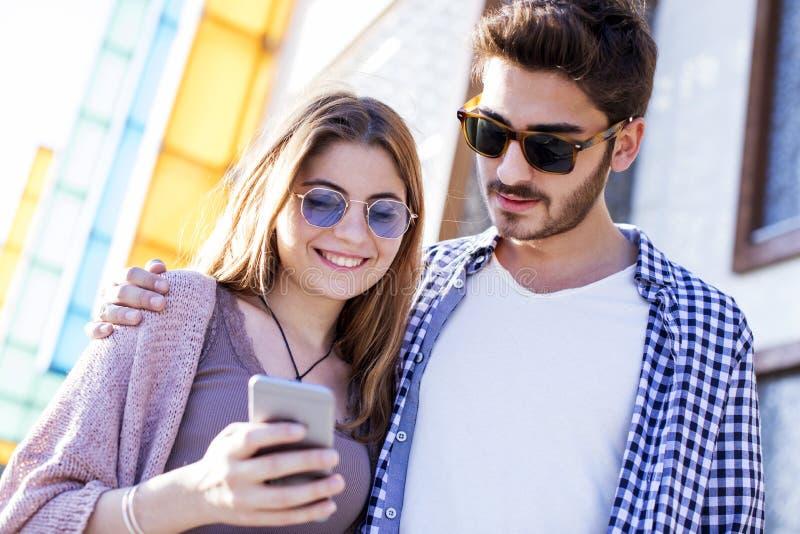 Junge Leute, die Handy auf Straße verwenden stockfotos