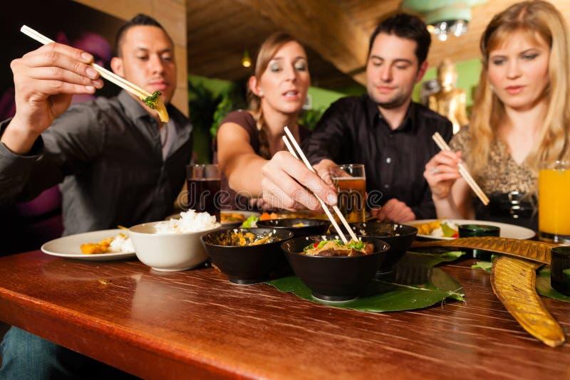 Junge Leute, die im thailändischen Restaurant essen stockbilder