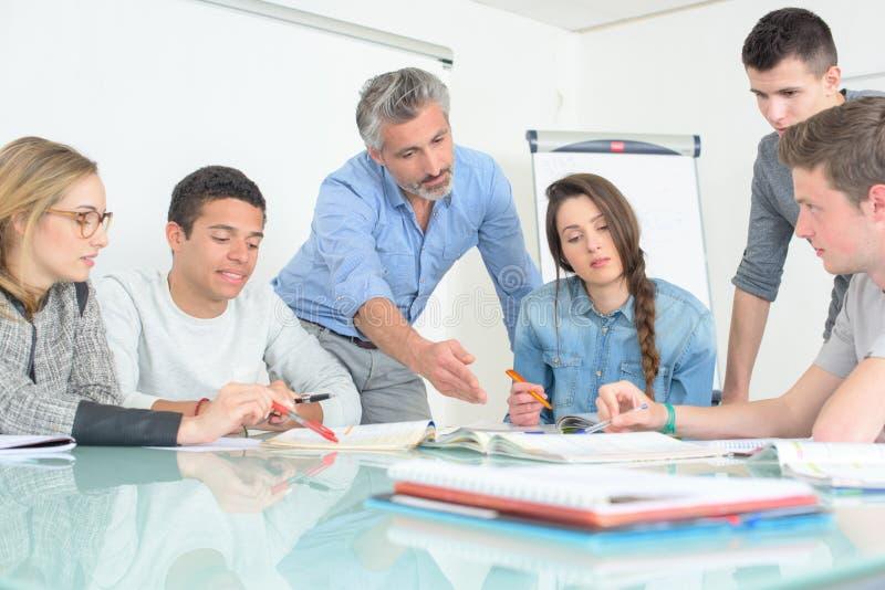 Junge Leute, die Lehrer sich besprechen, teilen Hochschulklassenzimmer mit lizenzfreie stockfotos