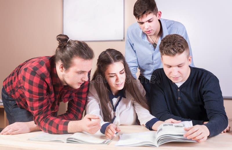 Junge Leute, die mit Büchern auf weißem Schreibtisch studieren Schöne Mädchen lizenzfreie stockbilder