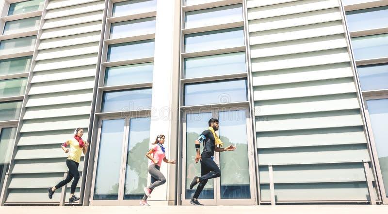 Junge Leute, die in modernes Stadtgebiet laufen - Eignungsmädchen, die mit männlichem Trainertrainer in der Stadt laufen - Sportk lizenzfreie stockfotografie