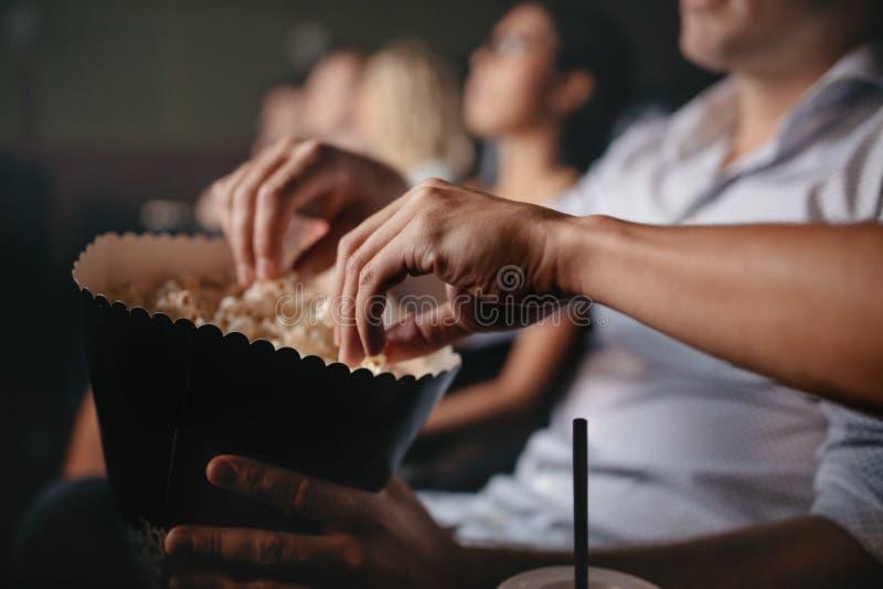 Junge Leute, die Popcorn im Kino essen lizenzfreie stockfotos