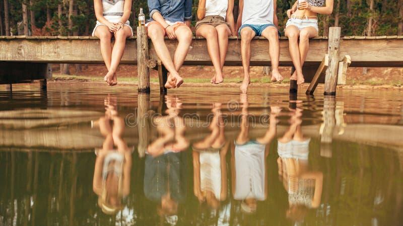 Junge Leute, die am Rand eines Piers sitzen stockbilder
