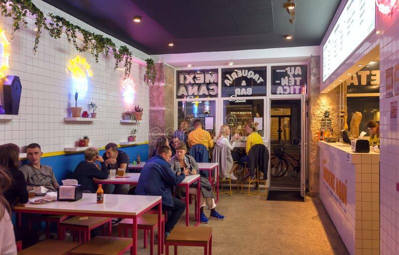 Junge Leute, die Schnellimbiß im Café oder moderne Artstange mit hellem Licht essen stockfotografie