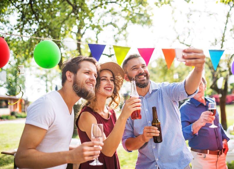 Junge Leute, die selfie an einer Partei draußen im Hinterhof nehmen stockfotos