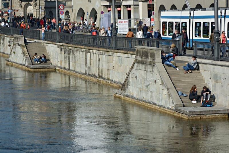 Junge Leute, die sonniges Wetter nahe Limmat-Fluss in Zürich genießen, stockfotos