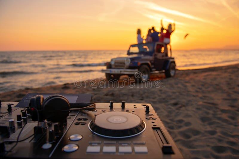 Junge Leute, die Spaß im konvertierbaren Auto am Strand am sunse haben lizenzfreie stockbilder
