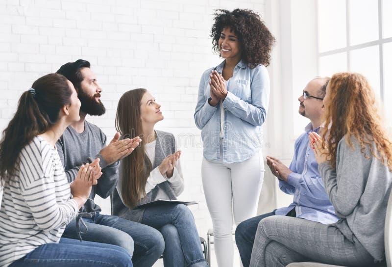 Junge Leute, die zur Frau bei der Rehabilitationsgruppensitzung klatschen lizenzfreies stockfoto
