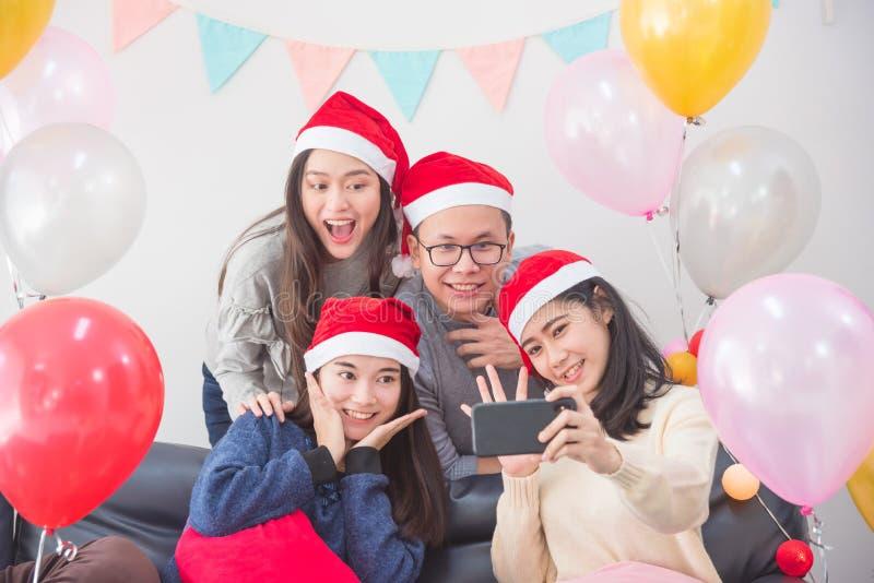 Junge Leute, ein Mann und drei Frauen, die Foto durch Handy in der Partei machen stockbilder