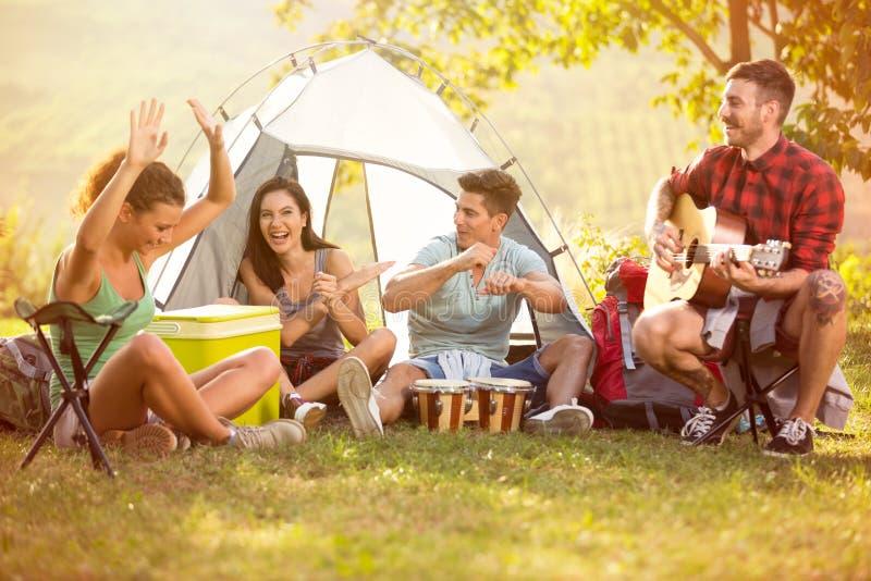 Junge Leute genießen in der Musik von Trommeln und von Gitarre auf Camping-Ausflug stockfotografie