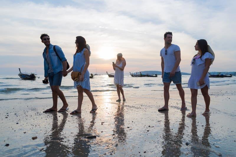 Junge Leute-Gruppe auf Strand an den Sonnenuntergang-Sommer-Ferien, Freund-gehende Küste stockfotos