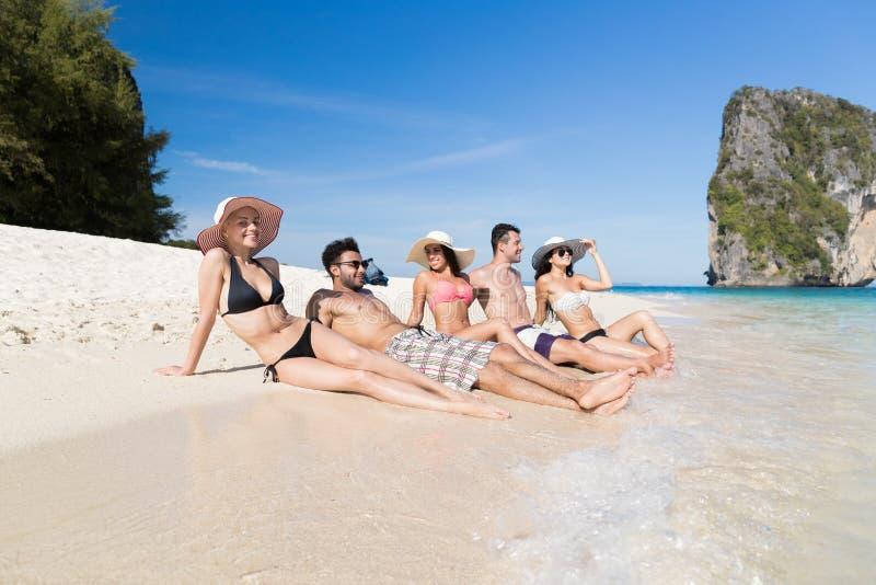 Junge Leute-Gruppe auf Strand-Sommer-Ferien, glückliche lächelnde Freund-Lügensand-Küste lizenzfreies stockfoto