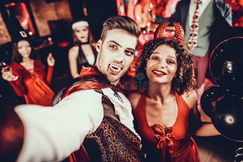 Junge Leute in Halloween-Kostümen, die Selfie nehmen stockfotografie
