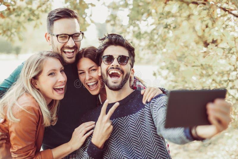 Junge Leute im Park mit der digitalen Tablette, die Spaß hat