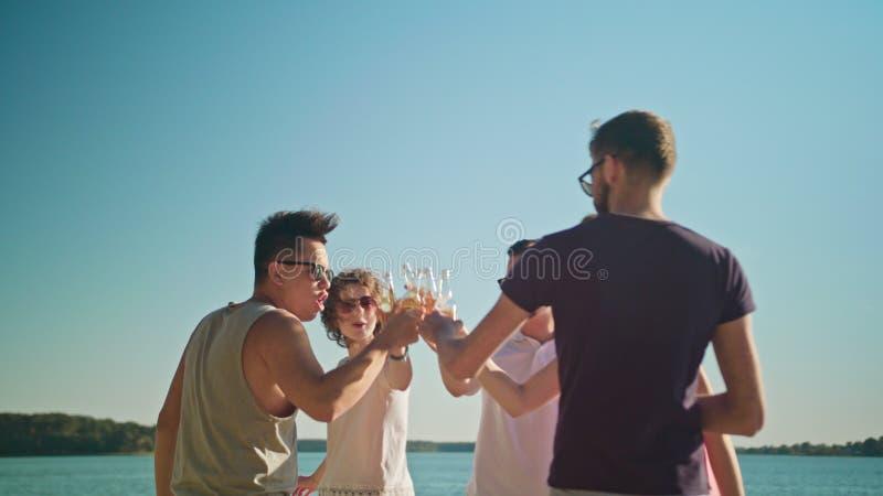 Junge Leute-klirrende Flaschen auf dem Strand stockbild