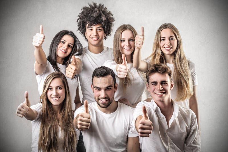 Junge Leute mit ihrem Daumen oben lizenzfreies stockfoto