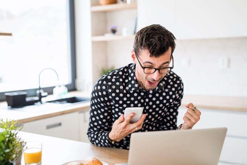 Junge Leute mit Laptop und Smartphone, die in der Küche sitzen und Aufregung ausdrücken stockfotografie