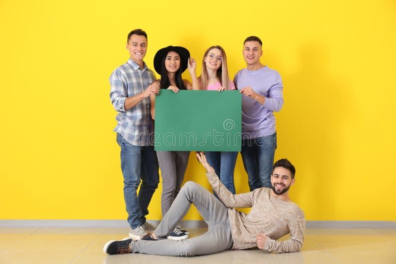 Junge Leute mit leerem Plakat nahe Farbwand stockfotos