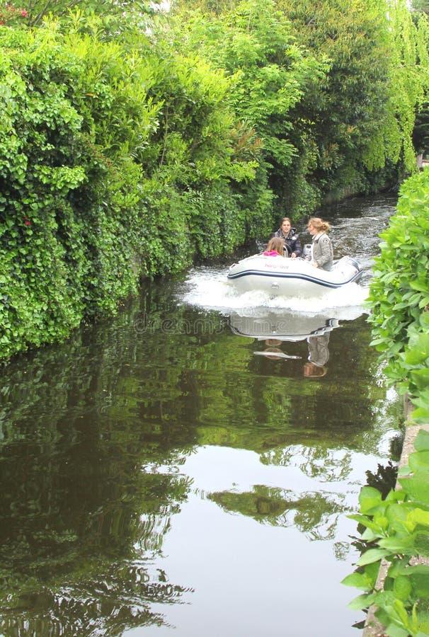 Junge Leute navigieren ein Motorboot, Holland stockbilder