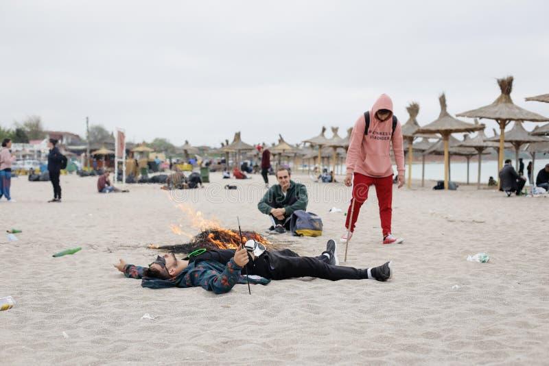 Junge Leute stehen auf dem Strand unter leeren Flaschen des Rückstands besonders still stockfoto