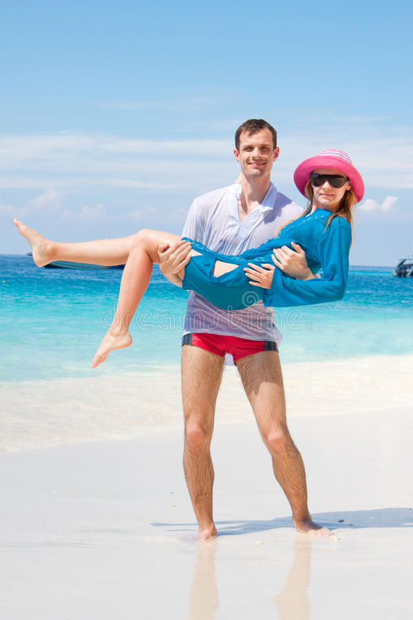 Junge Liebe Paare, die auf Seestrand lächeln stockbild