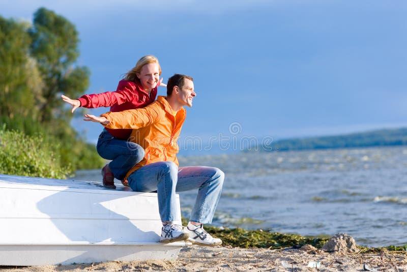 Junge Liebe Paare sitzen auf Boot auf Küste von Fluss lizenzfreie stockfotos