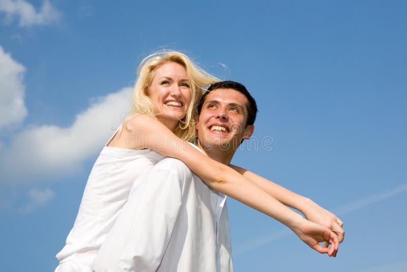 Junge Liebespaare, die unter Himmel lächeln stockbild