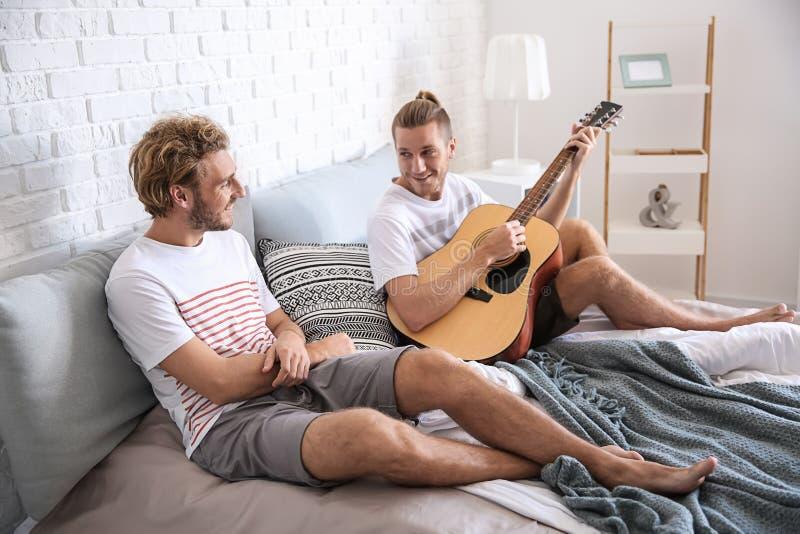 Junge liebevolle homosexuelle Paare, die zu Hause auf Bett stillstehen lizenzfreies stockfoto