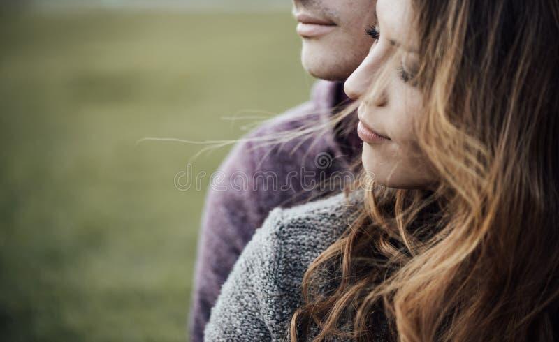 Junge liebevolle Paare, die auf dem Gras sitzen lizenzfreie stockbilder